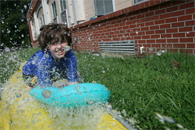 image of child playing on water slide