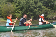 staff member and participants paddling in a canoe