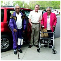 image of seniors standing outside of automobile