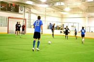 Adults playing indoor soccer.